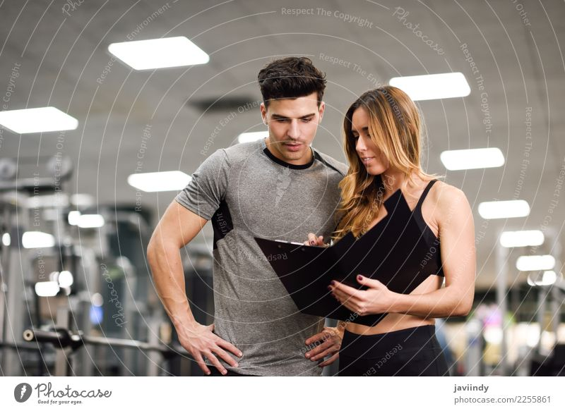 Personal trainer and client looking at his progress at the gym Woman Human being Youth (Young adults) Man Young woman Young man White 18 - 30 years Adults
