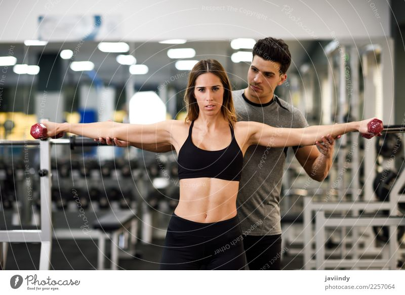 Personal trainer helping a young woman lift dumbells Woman Human being Youth (Young adults) Man Young woman Young man White 18 - 30 years Adults Lifestyle