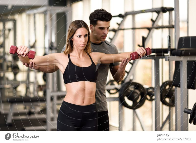 Personal trainer helping a young woman lift dumbells Lifestyle Body Sports Human being Masculine Feminine Young woman Youth (Young adults) Young man Woman