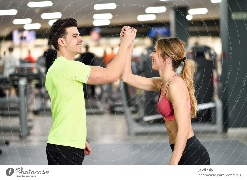 Smiling young man and woman doing high five in gym Lifestyle Happy Body Wellness Feasts & Celebrations Sports Success Human being Masculine Feminine Young woman