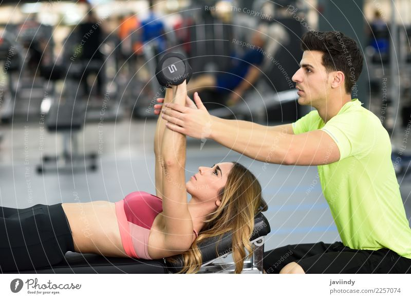 Personal trainer helping a young woman lift weights Woman Human being Youth (Young adults) Man Young woman Young man White 18 - 30 years Adults Lifestyle Sports