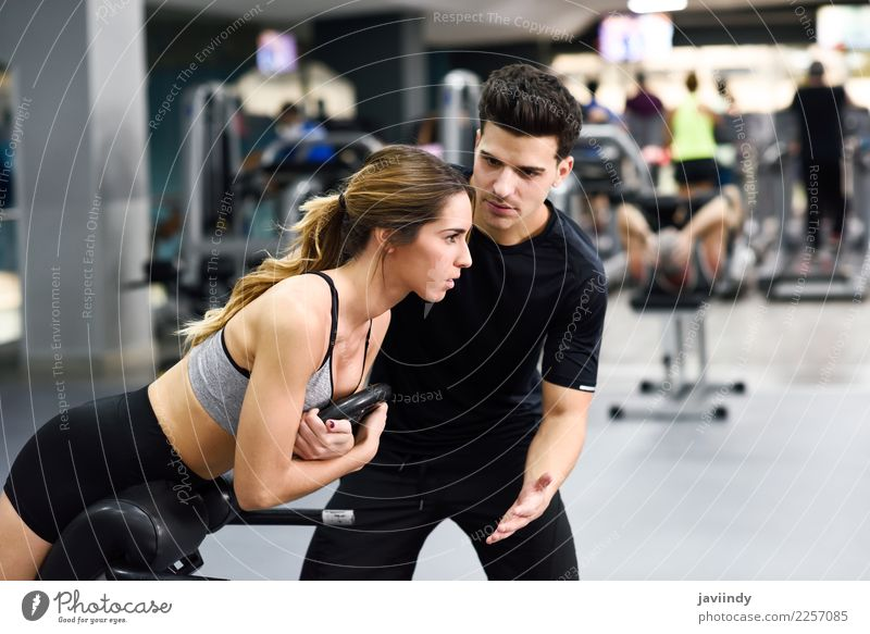 Personal trainer helping young woman lift weights Woman Human being Youth (Young adults) Man Young woman Young man White 18 - 30 years Adults Lifestyle Sports