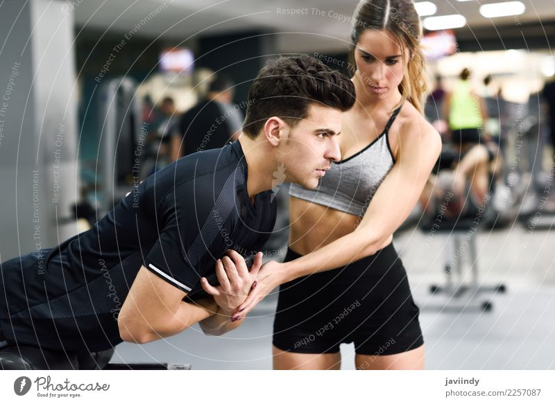 Female personal trainer helping a young man lift weights Lifestyle Body Sports Human being Masculine Feminine Young woman Youth (Young adults) Young man Woman