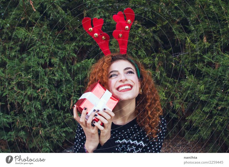 Young woman wearing winter clothes is holding a gift box Human being Nature Youth (Young adults) Christmas & Advent Beautiful Green Tree Red 18 - 30 years