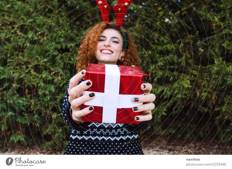 Young woman holding a christmas gift Human being Nature Youth (Young adults) Christmas & Advent Tree Joy Winter 18 - 30 years Adults Lifestyle Feminine Style