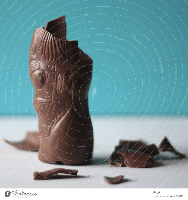 nibbled chocolate Santa Claus on a white table and blue wall Food Candy Chocolate Nutrition Lie Stand Authentic Simple Broken Small Delicious Sweet Blue Brown