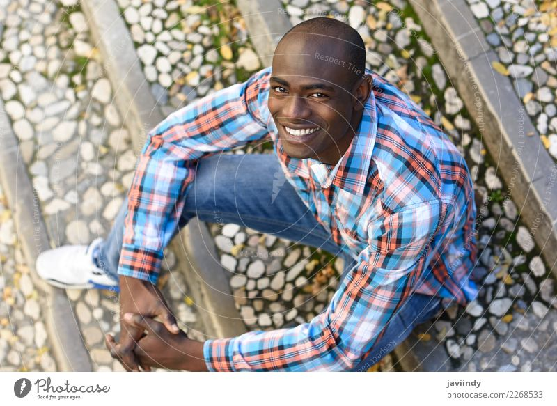 Black man smiling and sitting in urban steps Happy Beautiful Human being Masculine Young man Youth (Young adults) Man Adults 1 18 - 30 years Street Clothing