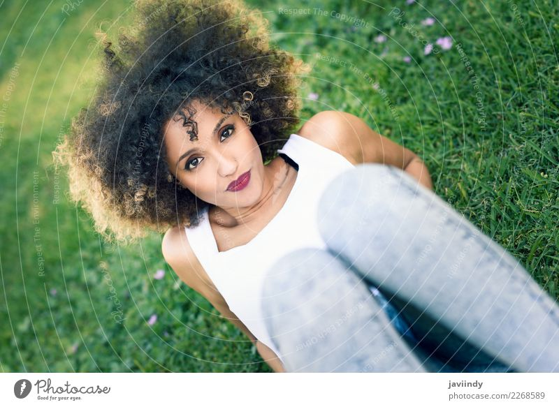 Mixed woman with afro hairstyle sitting in urban park Lifestyle Style Happy Beautiful Hair and hairstyles Face Summer Human being Feminine Young woman