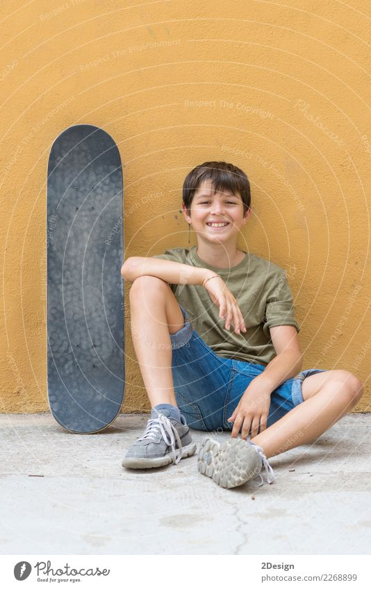 A smiling boy with skateboard sitting alone on the floor Child Human being Man Summer Sun Relaxation Joy Street Adults Lifestyle Spring Natural Boy (child)