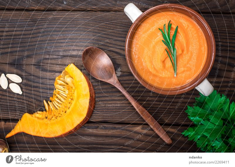fresh pumpkin soup in a ceramic plate Vegetable Soup Stew Herbs and spices Eating Lunch Dinner Vegetarian diet Bowl Spoon Table Hallowe'en Nature Wood Fresh Hot