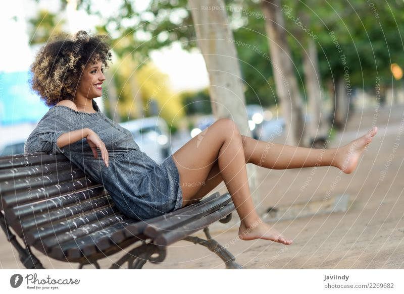 Woman with afro hairstyle sitting on a bench moving her legs Human being Youth (Young adults) Young woman Beautiful Joy 18 - 30 years Black Face Street Adults