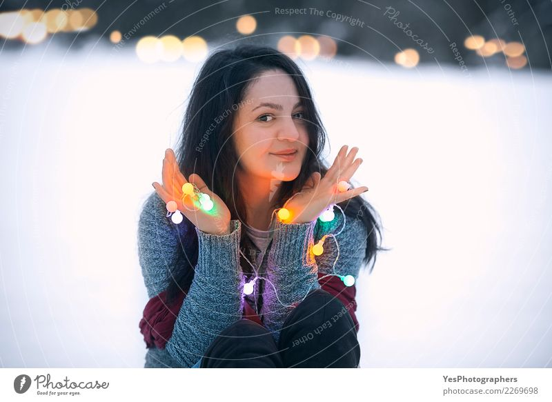 Smiling brunette woman holding string lights Lifestyle Joy Beautiful Leisure and hobbies Winter Snow Decoration Feasts & Celebrations New Year's Eve Young woman