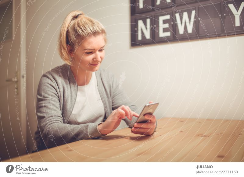 Young woman is browsing the web with her phone Lifestyle Shopping Living or residing Flat (apartment) Interior design Room Living room Human being Feminine
