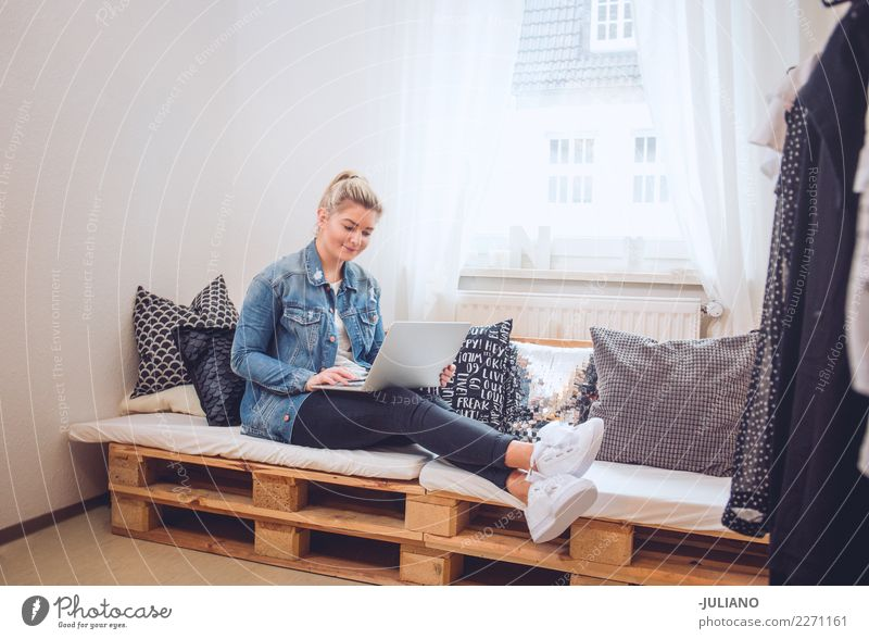 Young woman sitting on diy couch with notebook Human being Youth (Young adults) Joy 18 - 30 years Adults Lifestyle Interior design Feminine Business Moody