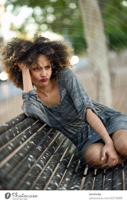 Funny black woman with afro hairstyle sitting on an urban bench Woman Human being Youth (Young adults) Young woman Beautiful 18 - 30 years Black Face Street