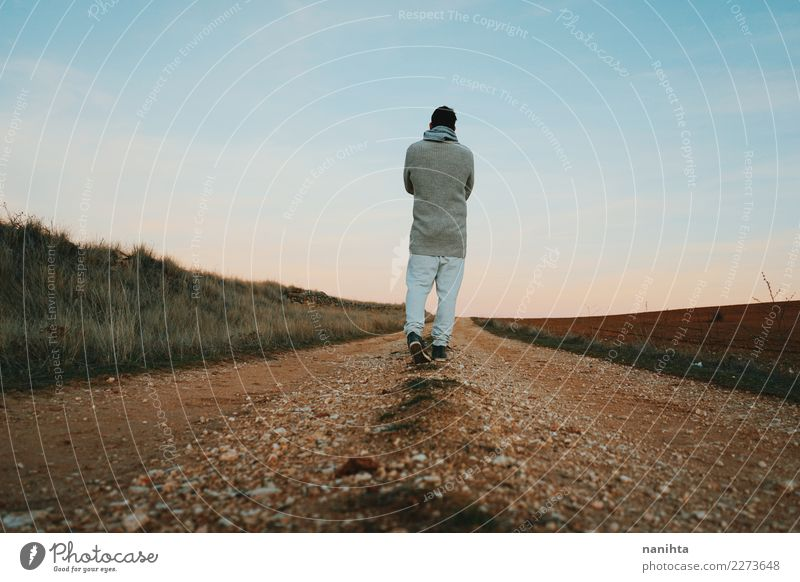 Back view of a man walking along a rural path Human being Sky Nature Man Beautiful Landscape Relaxation Far-off places Adults Lifestyle Environment Healthy