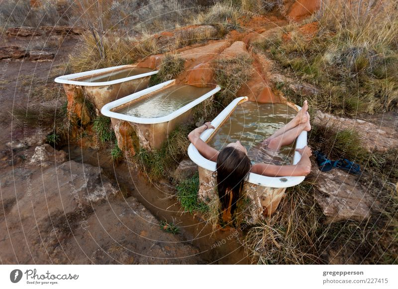 Young woman relaxing in a natural hot springs.. Relaxation Contentment Swimming & Bathing Bathtub Meditation Well-being Personal hygiene Wash Spa Perspective