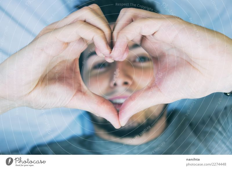 Young man making a heart shape with his hands Human being Youth (Young adults) Man Blue Beautiful Adults Healthy Love Health care Hair and hairstyles Together
