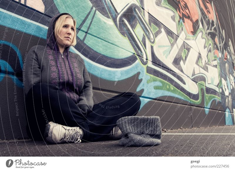 Human being Woman Youth (Young adults) Adults Wall (building) Graffiti Wall (barrier) Blonde Facade Sit Poverty Characters Gloomy 18 - 30 years Jeans Young woman