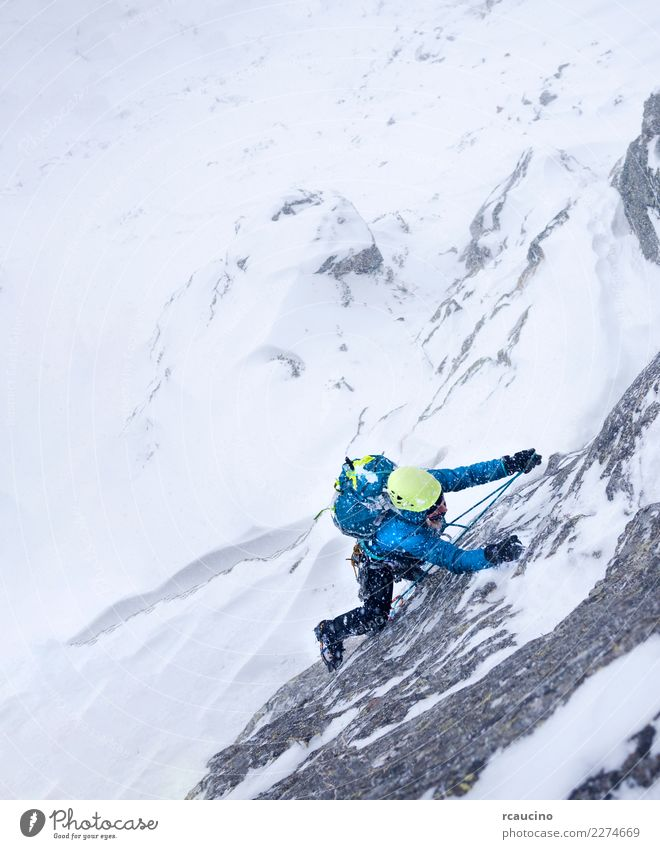 Female climber in the storm during an extreme winter climb Adventure Expedition Winter Snow Mountain Sports Climbing Mountaineering Success Woman Adults Storm