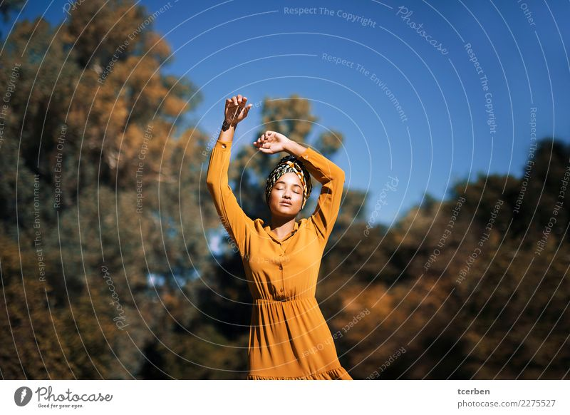 Portrait of a mulatto woman with headscarf and raised arms Human being Sky Youth (Young adults) Young woman Blue Colour Beautiful Sun Tree Calm 18 - 30 years
