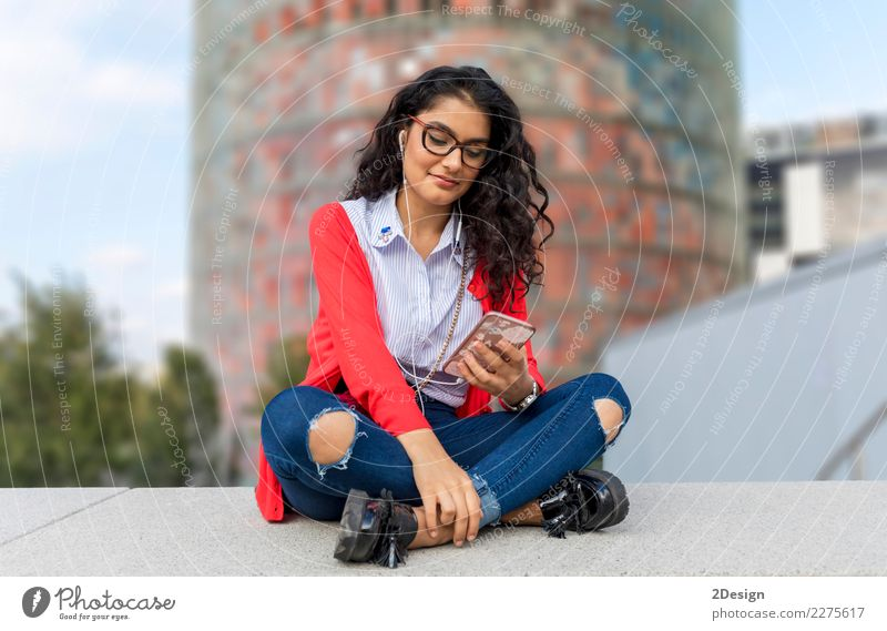 A young woman listening music on digital tablet sitting Joy Freedom Sun Entertainment Music Telephone MP3 player Technology Woman Adults Youth (Young adults)