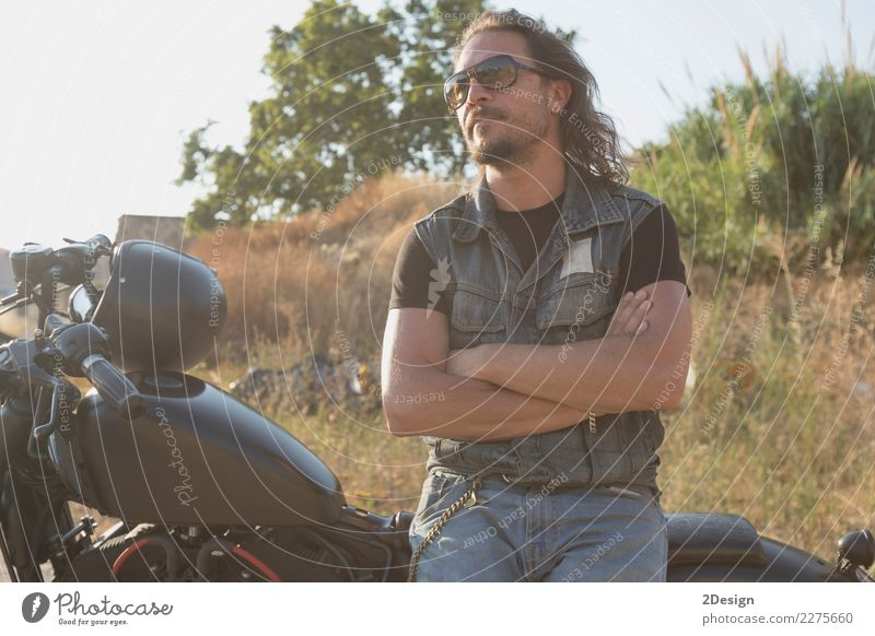 Long-haired brunette guy in sunglasses jeans and a jeans shirt posing on a black custom motorcycle Lifestyle Beautiful Vacation & Travel Trip Adventure Freedom