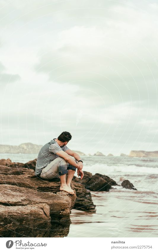 Man sitting near the sea in a cloudy day Human being Nature Vacation & Travel Youth (Young adults) Water Young man Ocean Relaxation Clouds Winter Far-off places