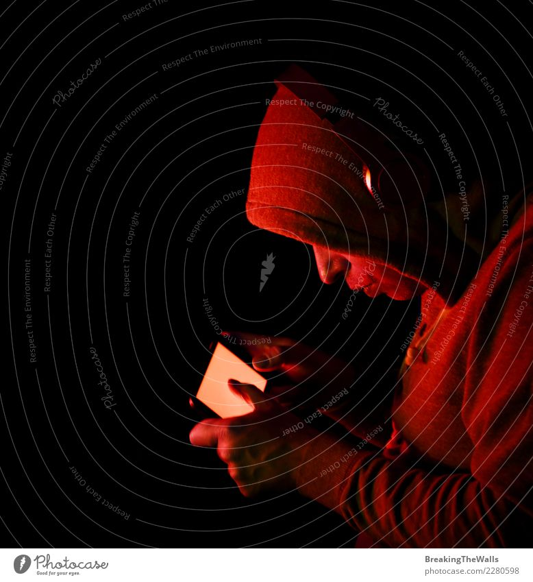 Man in hoodie holding smartphone over black background Lifestyle Leisure and hobbies Playing Computer games Entertainment Music Cellphone Screen
