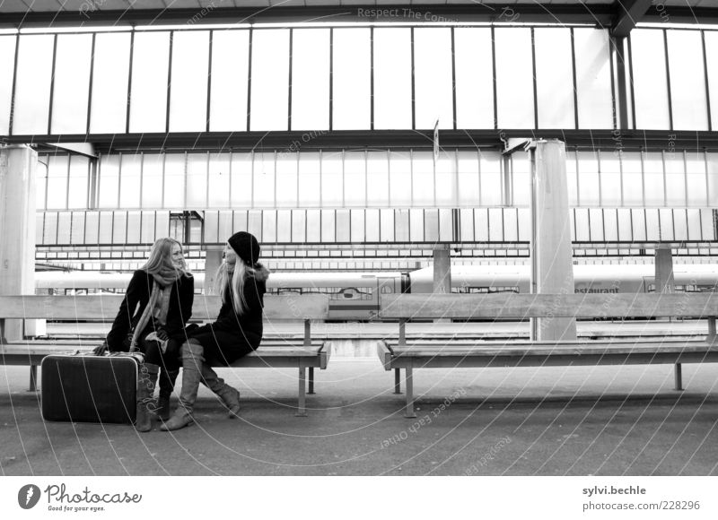Human being Youth (Young adults) Winter To talk Friendship Together Sit Wait Bench Young woman Railroad tracks Train station Coat Goodbye Suitcase Passenger traffic