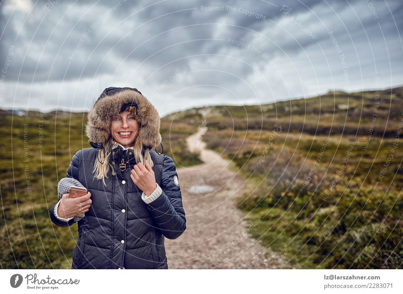 Middle-aged woman braving a cold winter in nature Happy Winter Telephone Cellphone Woman Adults Nature Landscape Sky Storm Wind Coat Smiling breezy walking