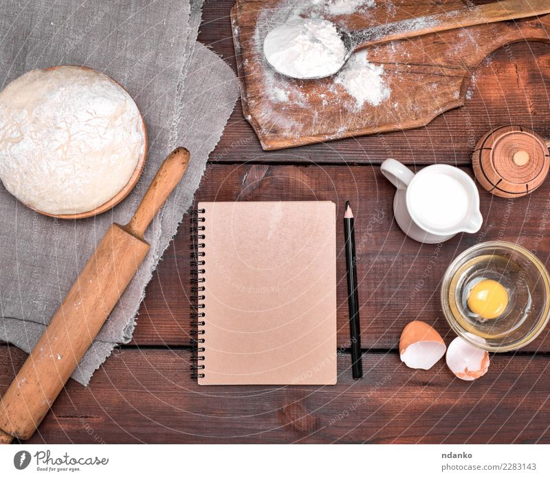 dough and ingredients Dough Baked goods Bread Bowl Table Kitchen Paper Wood Eating Fresh Natural Above Brown White Pencil notebook recipe Menu Rolling pin Yeast