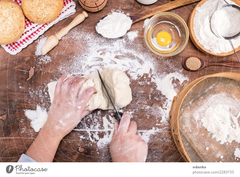 female hands cut with a knife yeast dough Dough Baked goods Bread Roll Bowl Body Table Kitchen Woman Adults Arm Hand Sieve Wood Make Fresh Natural Above Brown