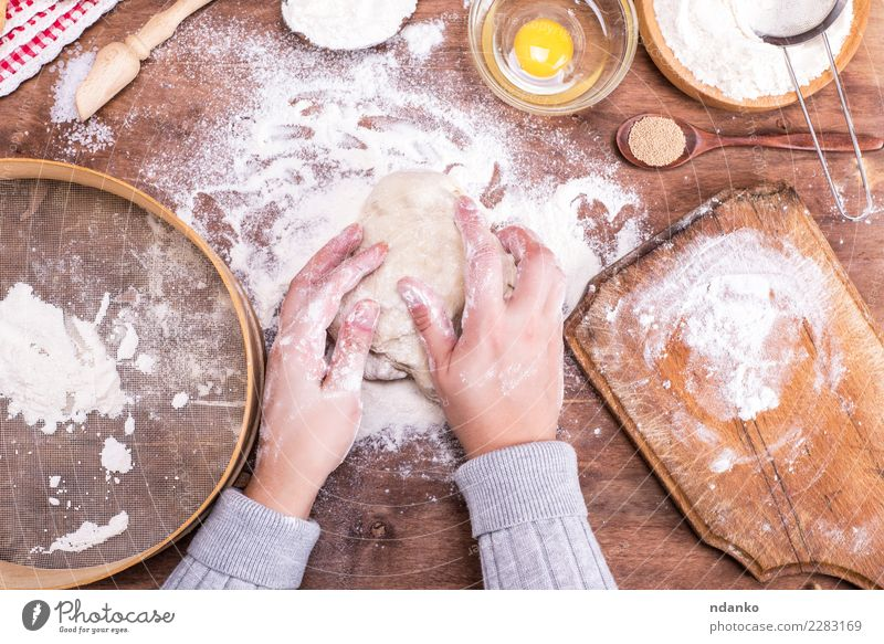 hands interfere with a ball of yeast dough Dough Baked goods Bread Bowl Spoon Body Table Kitchen Arm Hand Sieve Wood Eating Fresh Natural Above Brown White