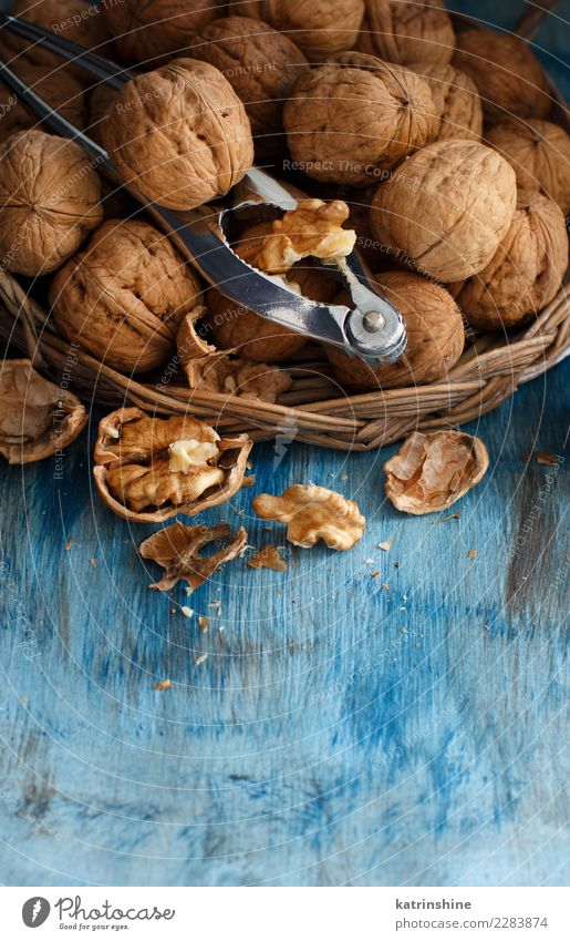 Fresh walnuts with a nutcracker Nutrition Vegetarian diet Table Group Old Natural Blue Brown Gray antioxidant appetizer broken Crack & Rip & Tear food health