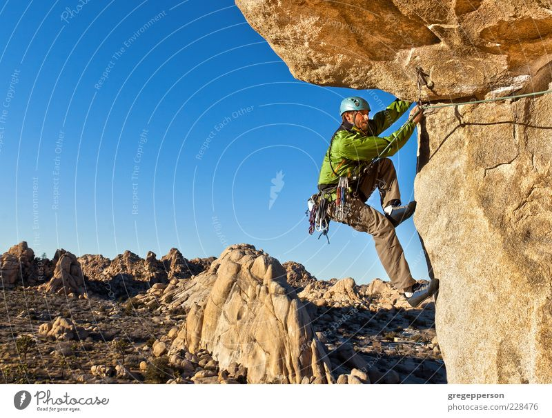 Rock climber clinging to a cliff. Human being Nature Landscape Mountain Freedom Power Tall Hiking Adventure Rope Success Climbing Peak Brave Athletic Balance