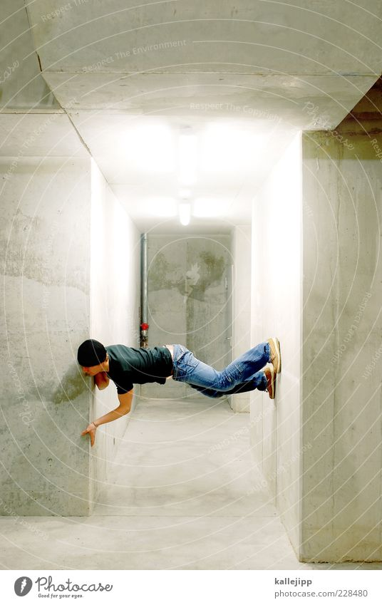 footnote Human being Masculine Man Adults 1 Wall (barrier) Wall (building) T-shirt Jeans Footwear Cap Cold Parkour Neon light Concrete wall Colour photo