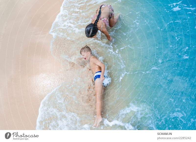 Cute boy and girl having fun on the sunny tropical beach. Lying on sand, wonderful waves around them. View from above Lifestyle Joy Freedom Summer Island Child
