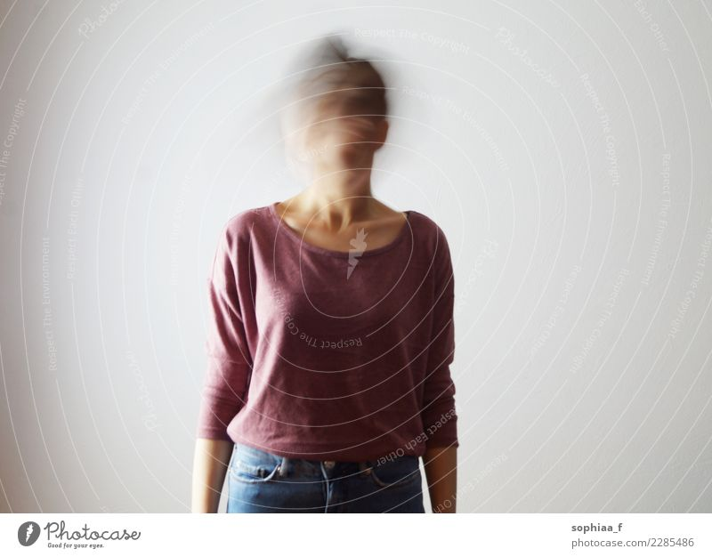 Who am I? Portrait of confused young woman with blurred face. She is moving her head fast, so her face isn't identifiable. Motion blur. who am i confusion