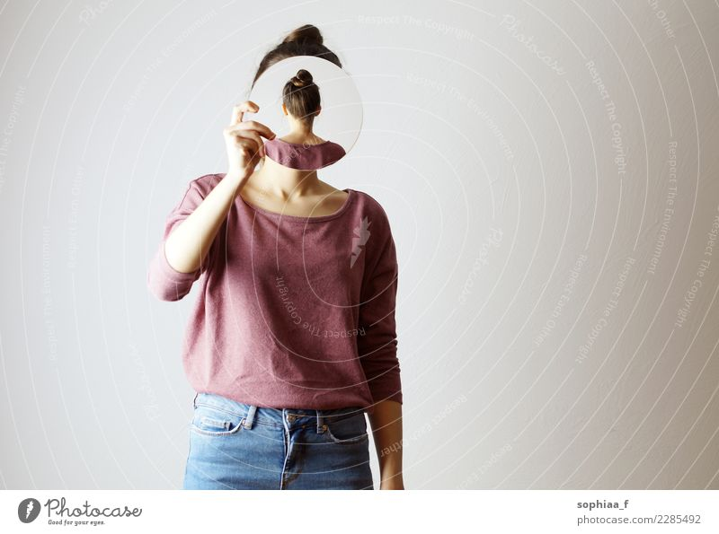 Who am I? Young woman holding a mirror in front of her face. Faceless, identity not recognizable, the mirror is showing her backhead. Hiding her face. who am i