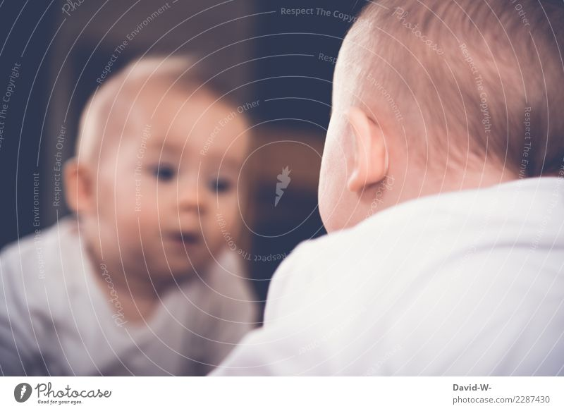 Baby looks in the mirror and discovers his reflection Mirror Mirror image inquisitive explore inquisitorial curious Curiosity Cute Infancy Child Observe