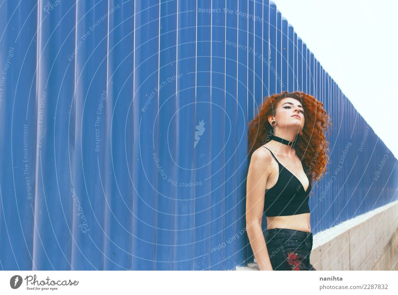 Young redhead woman leaning against a blue wall Human being Youth (Young adults) Young woman Blue Town Beautiful Relaxation 18 - 30 years Adults Lifestyle