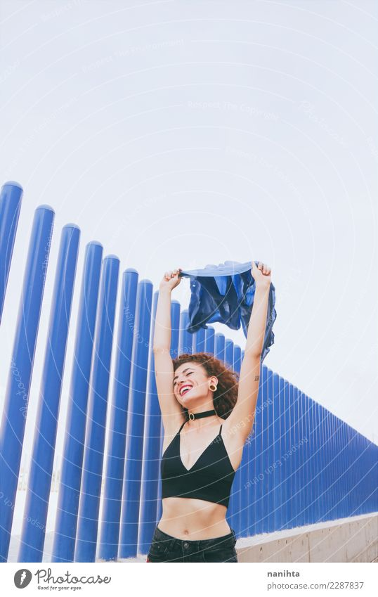 Young cheerful woman waving a blue flag Human being Youth (Young adults) Young woman Blue Joy 18 - 30 years Adults Life Lifestyle Wall (building) Feminine Style