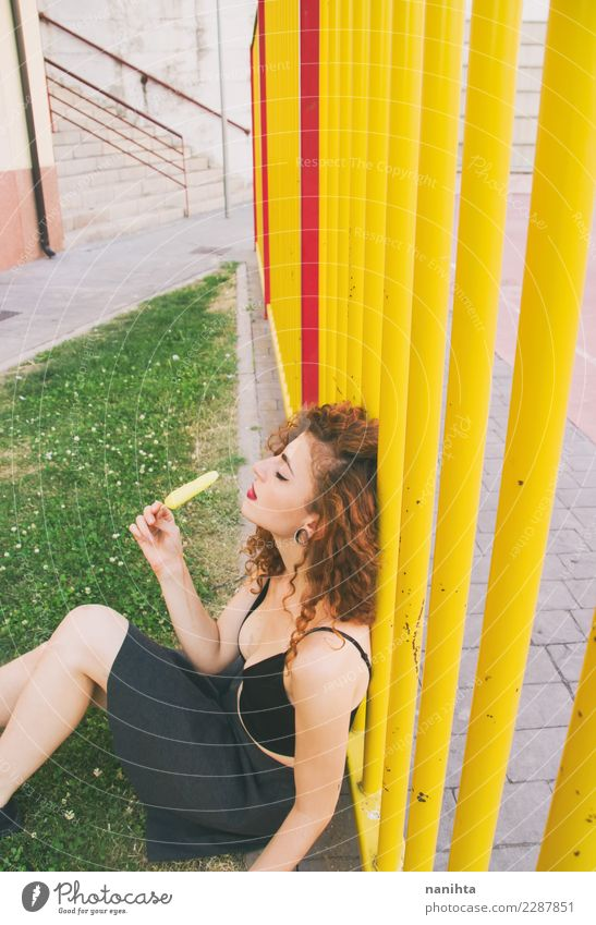 Young woman in a park enjoying a lemon ice cream Food Ice cream Eating Lifestyle Style Design Body Hair and hairstyles Wellness Senses Relaxation Schoolyard