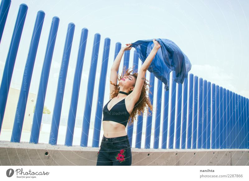 Young woman raising her arms in a windy day Human being Youth (Young adults) Blue Beautiful Joy 18 - 30 years Adults Life Lifestyle Wall (building) Feminine