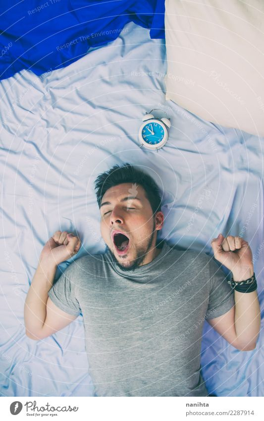 Young man yawning in his bed Human being Youth (Young adults) Man Blue Relaxation Adults Lifestyle Healthy Time Moody Work and employment Clock Masculine Lie