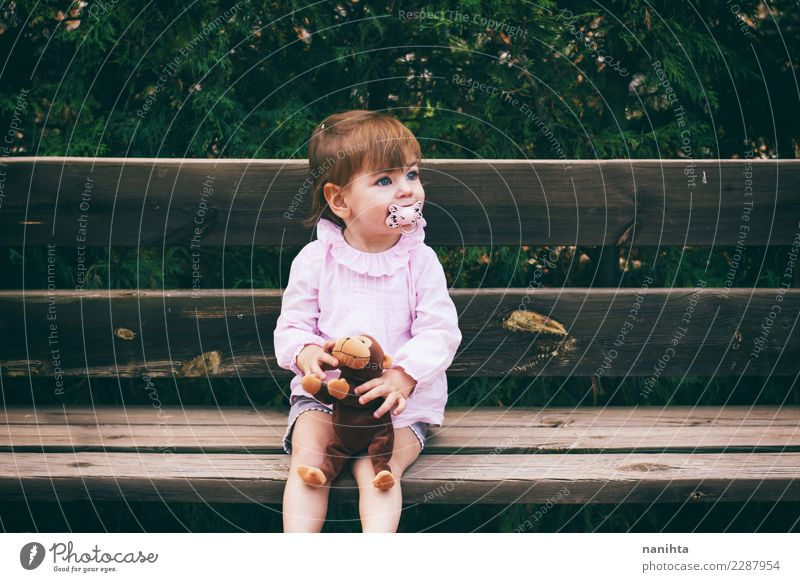 Lovely little girl sitting in a wooden bench Human being Nature Beautiful Relaxation Joy Girl Lifestyle Environment Feminine Wood Leisure and hobbies Park