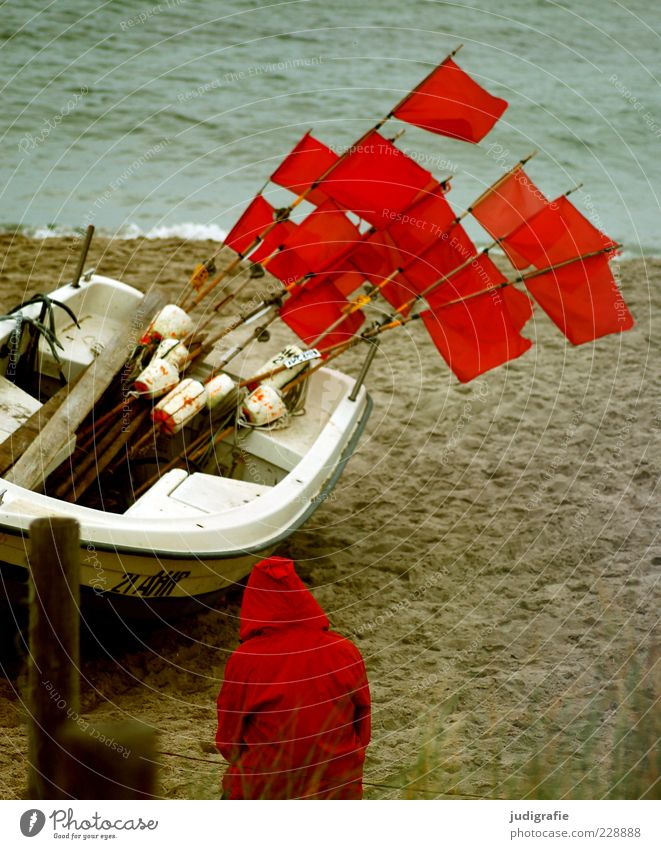 Red on the beach Human being 1 Environment Nature Landscape Climate Coast Beach Baltic Sea Ocean Fishing boat Sit Wait Moody Flag Hooded (clothing) Rain jacket