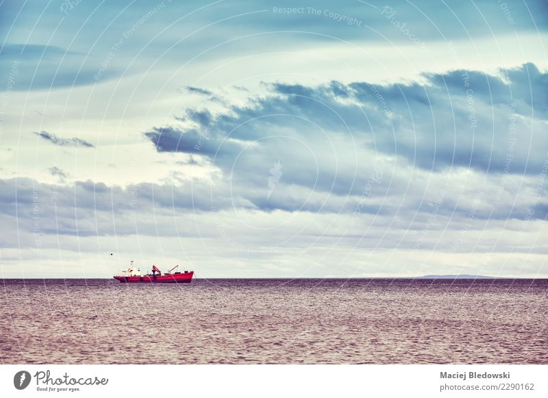 Lonely ship, color toned picture, Chile. Vacation & Travel Trip Cruise Ocean Nature Landscape Sky Storm clouds Waves Coast Transport Fishing boat Watercraft