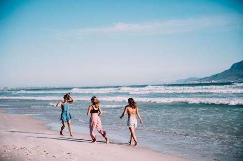 Group of younf adult friends walking on the beach Joy Happy Vacation & Travel Summer Beach Ocean Woman Adults Friendship Smiling Together Surfing holiday